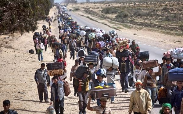 FOR USE AS DESIRED, YEAR END PHOTOS - FILE -In this March 4, 2011 file photo, men from Bangladesh, who used to work in Libya but recently fled the unrest, walk with their belongings alongside a road, as they head to a refugee camp after crossing the